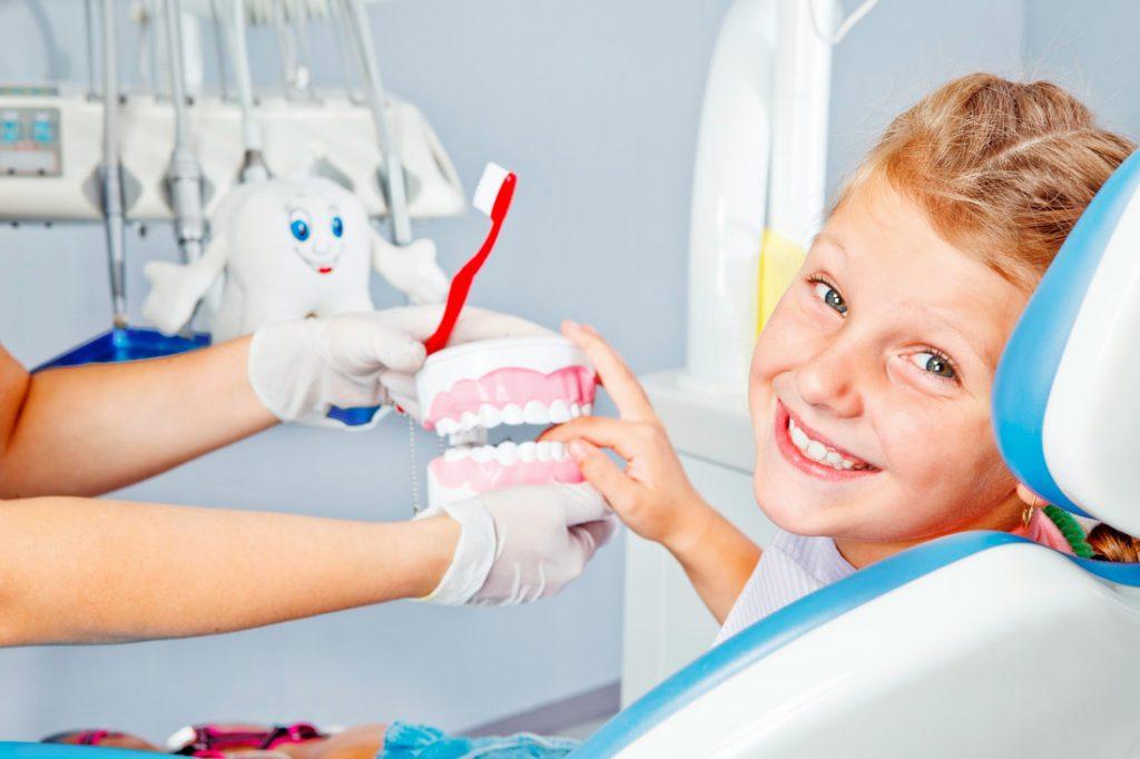 menino-sorrindo-dentista-mao-dentadura-escova-dente.jpg